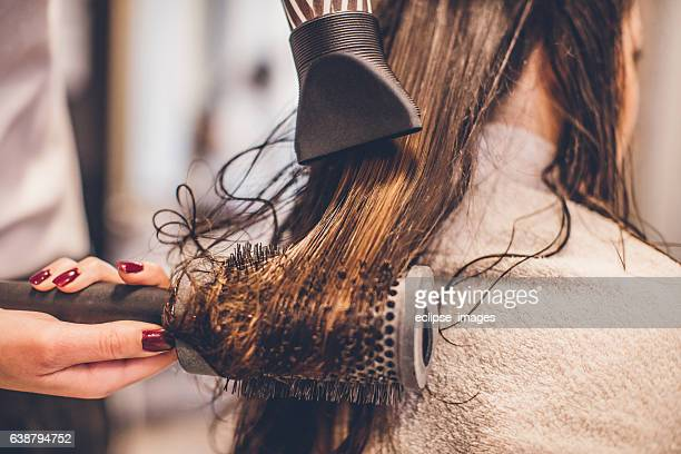 woman drying hair with a hair dryer and brush... - secador de cabelo - fotografias e filmes do acervo