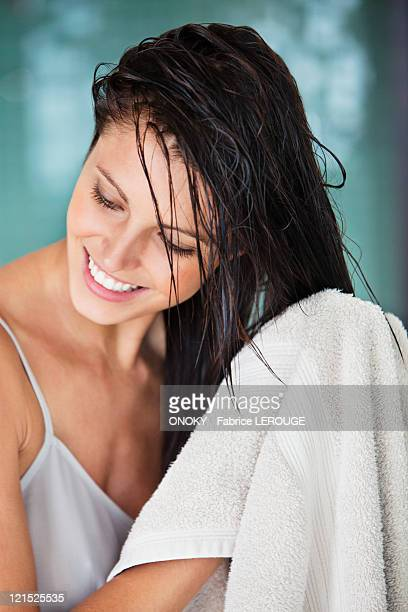 Woman drying her hair with a towel
