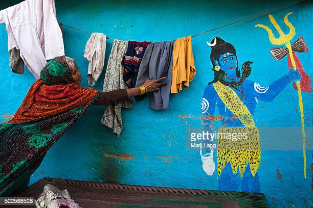 A woman drying laundry by the wall of her colorful house painted with the Hindu god Shiva New Delhi Delhi India