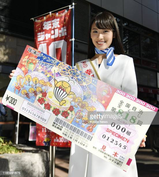 """Woman dubbed """"lady luck"""" holds a large sample of a year-end """"Jumbo"""" lottery ticket to promote the lottery in Tokyo's Ginza shopping district on Nov...."""