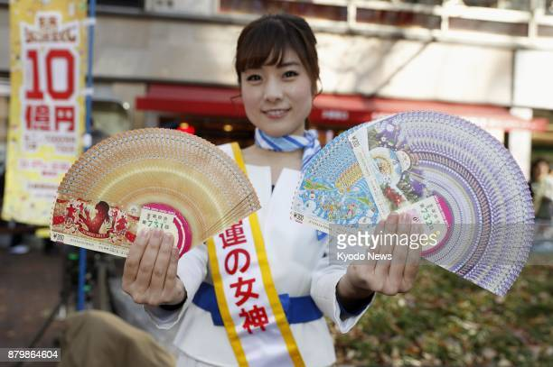 A woman dubbed 'lady luck' holds yearend 'Jumbo' lottery tickets near a lottery booth in Tokyo's Ginza district on Nov 27 2017 The 300yen tickets...