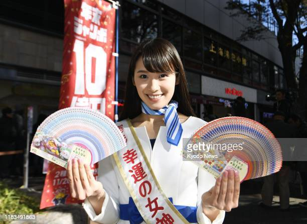 """Woman dubbed """"lady luck"""" holds year-end """"Jumbo"""" lottery tickets to promote the lottery in Tokyo's Ginza shopping district on Nov. 20, 2019."""