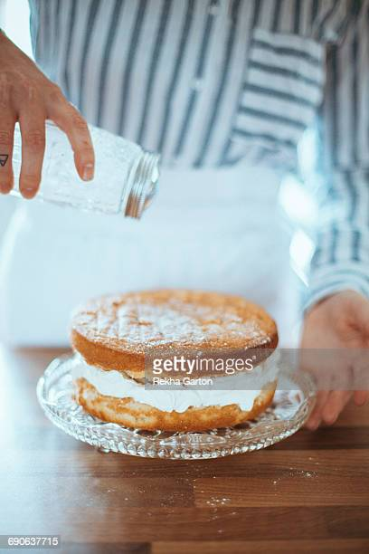 woman dusting a cake - rekha garton stock pictures, royalty-free photos & images