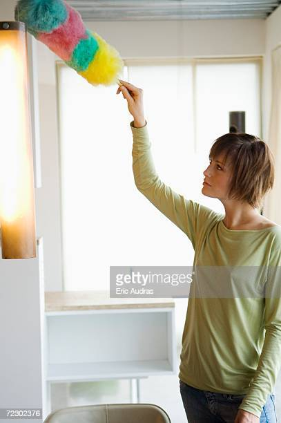 Woman dusting a lamp with a feather duster