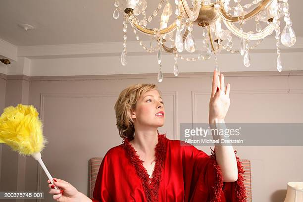 Woman dusting chandelier, close-up