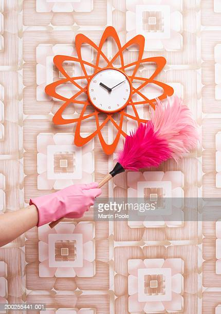 Woman dusting clock hanging on patterned wall, close-up