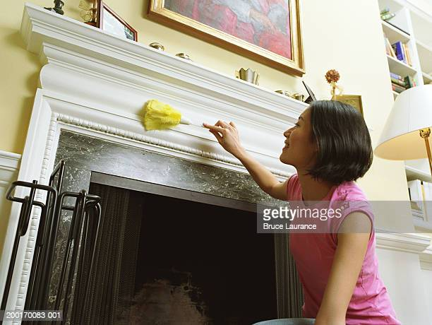 Woman dusting fireplace, low angle view
