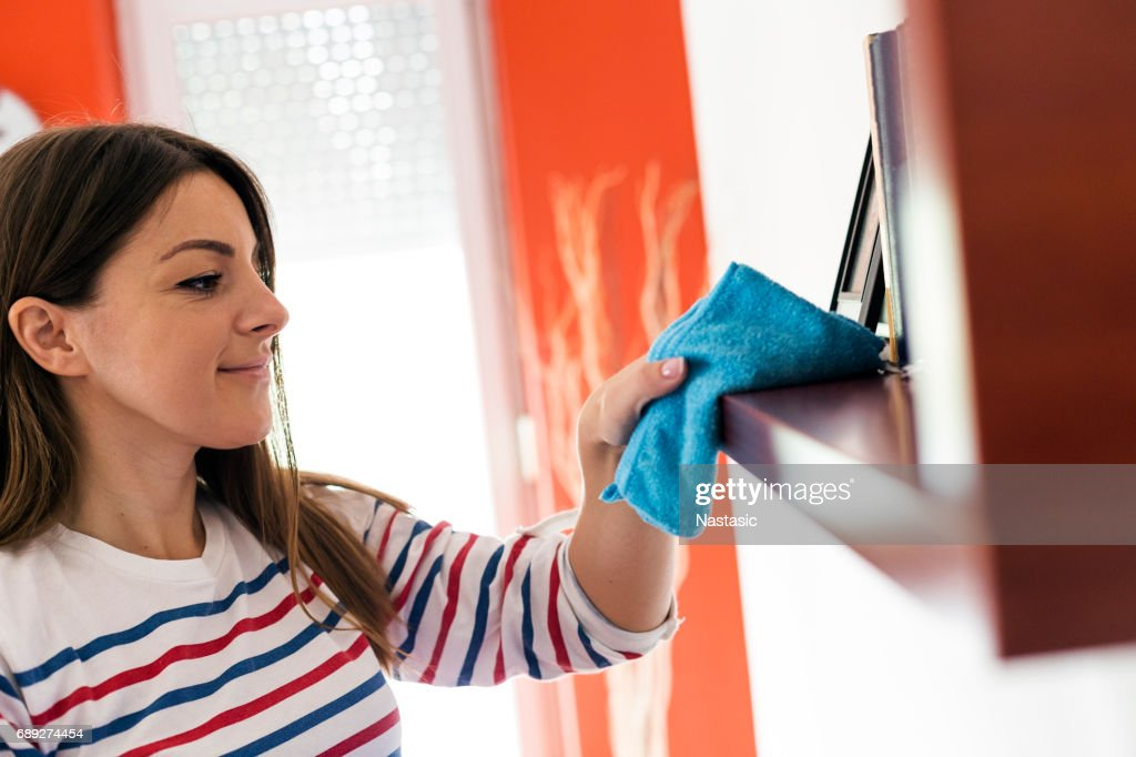 Woman dusting shelf : Stock Photo