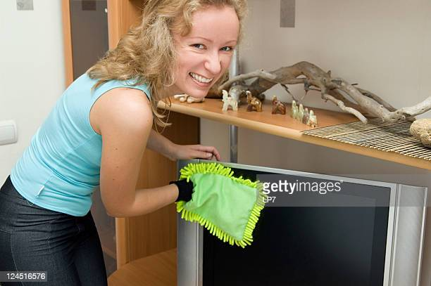 woman dusting tv - tv housewife stock photos and pictures