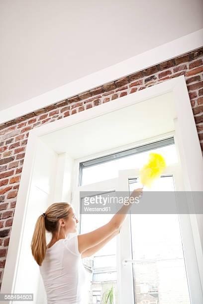 Woman dusting window