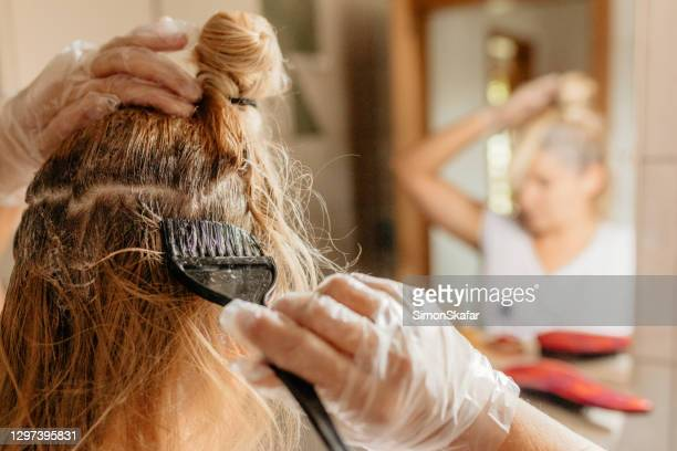 frau färbt haare vor dem spiegel - färbemittel stock-fotos und bilder