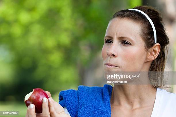 Woman eat an apple after her workout