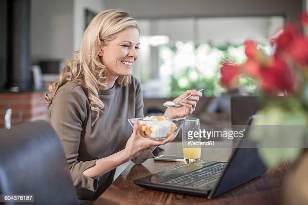 Woman eathing fruit salad working at home on laptop
