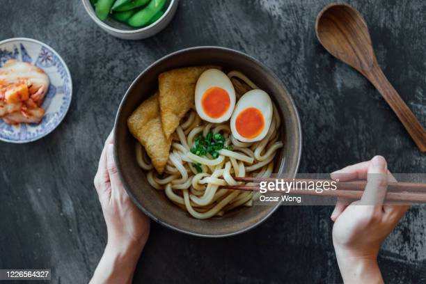 woman eating a bowl of traditional vegetarian japanese udon noodles - ramen noodles stock pictures, royalty-free photos & images