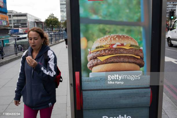 Woman eating a burger while passing an advertisement for burgers at Elephant and Castle in London, UK. The area is now subject to a master-planned...