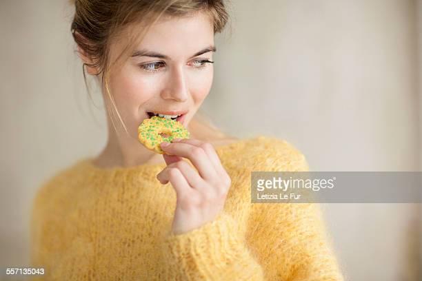 woman eating a cookie - kuchen und süßwaren stock-fotos und bilder