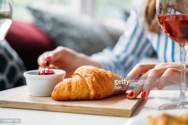 Woman eating a croissant with jam
