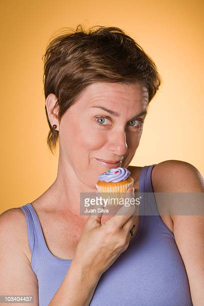 Woman eating a cupcake, smiling, portrait
