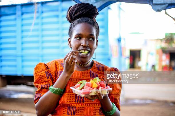 woman eating a fruit salad - nairobi stock pictures, royalty-free photos & images