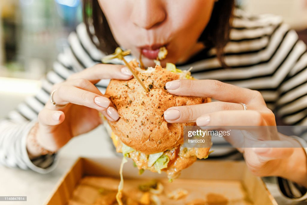 Woman eating a hamburger in modern fastfood cafe, lunch concept : Stock Photo