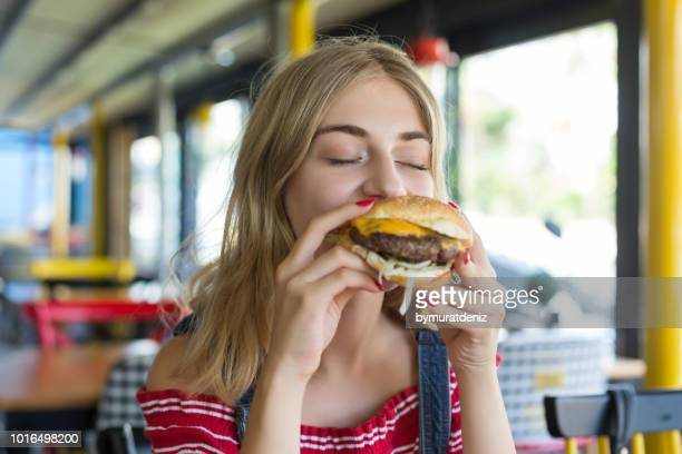 woman eating a hamburger - cheeseburger stock pictures, royalty-free photos & images