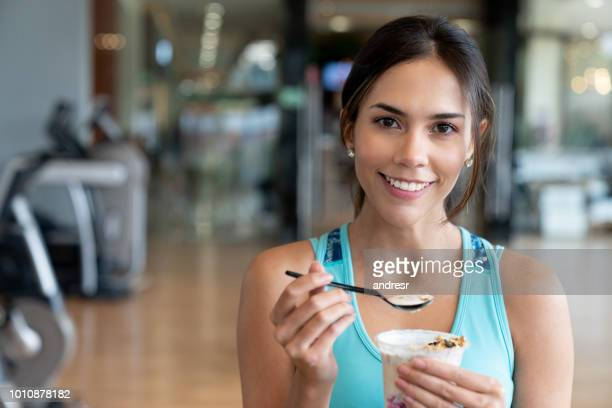 woman eating a healthy snack at the gym - yoghurt stock pictures, royalty-free photos & images