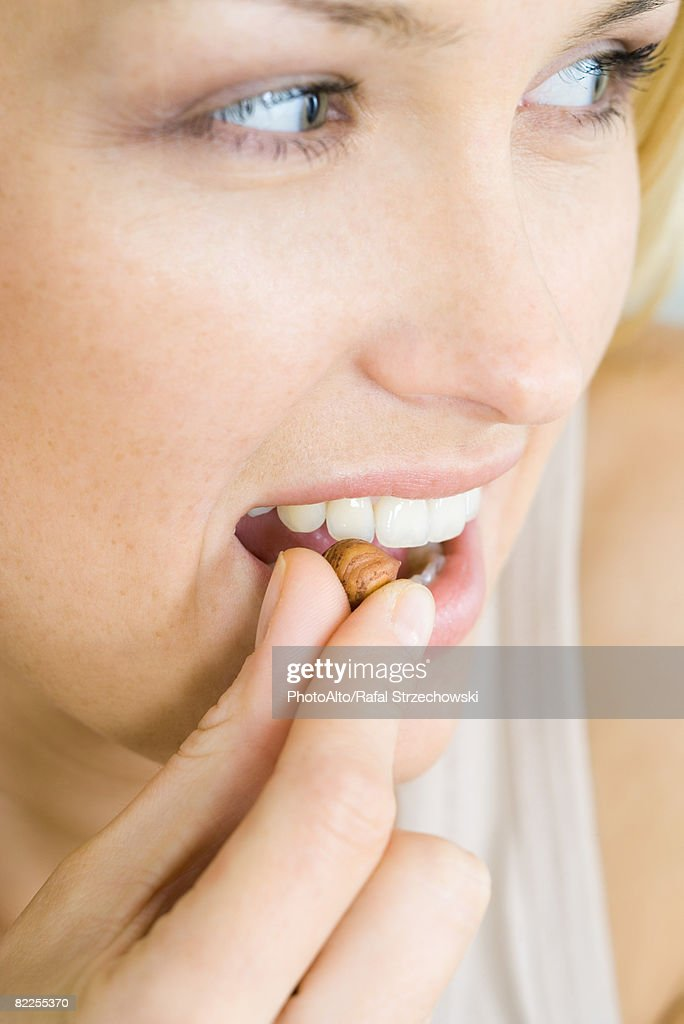 Woman eating a nut, looking away, headshot, portrait : Stock Photo