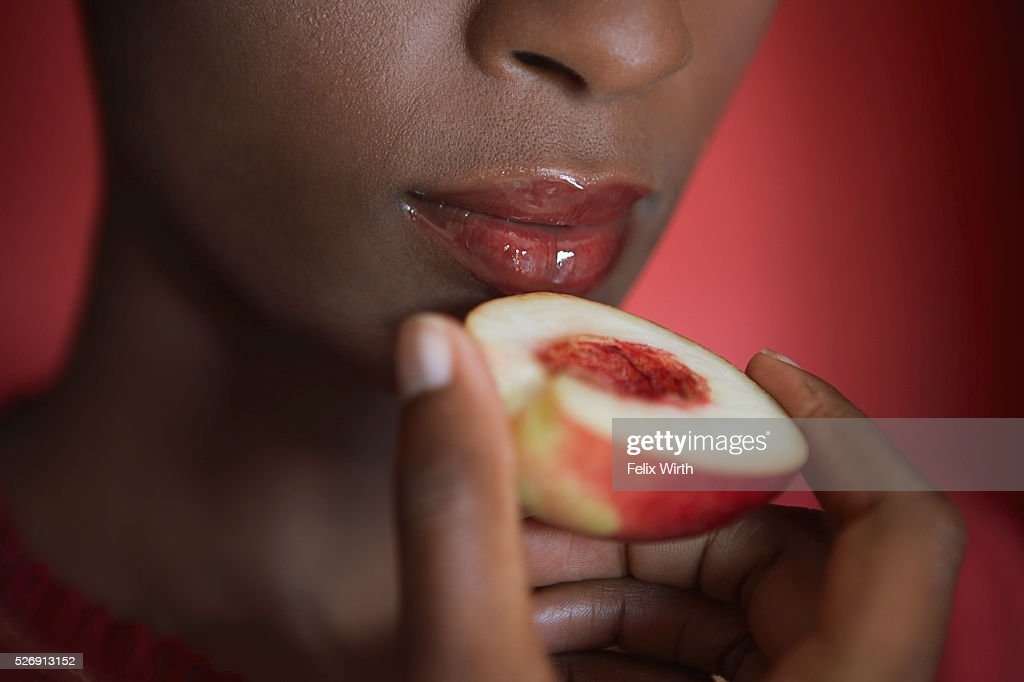Woman eating a peach : Foto de stock
