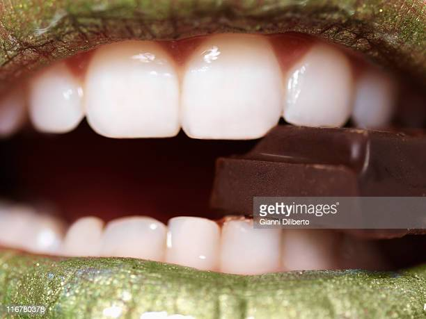 A woman eating a piece of chocolate, extreme close up of mouth
