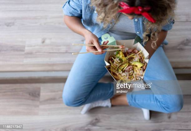 woman eating a poke bowl at home while moving house - food delivery foto e immagini stock