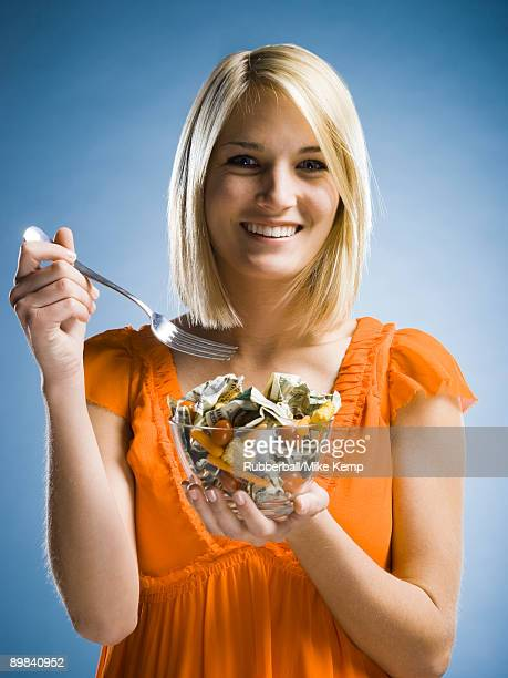woman eating a salad made of money