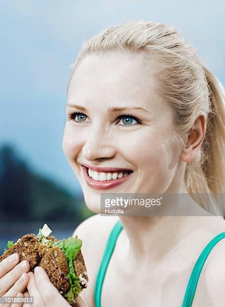 a woman eating a sandwich on 7-grain bread - pane integrale foto e immagini stock