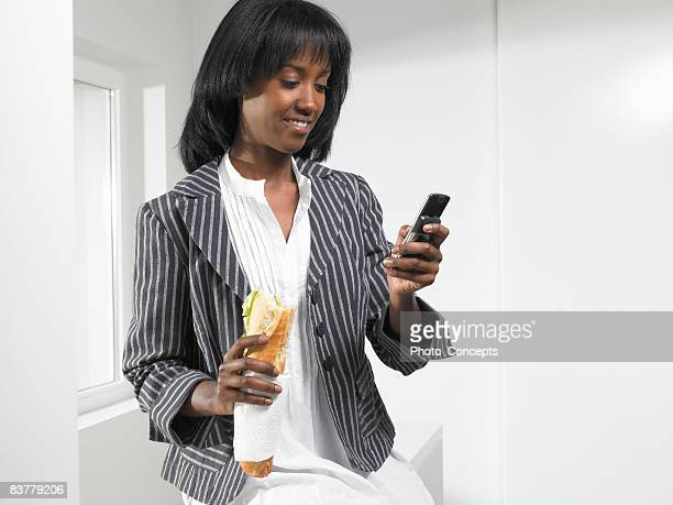 Woman eating a sandwich, on the phone