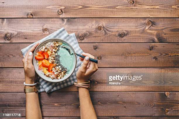 vrouw eet een smoothie bowl gegarneerd met verse bessen, granola en chia zaden - table top shot stockfoto's en -beelden