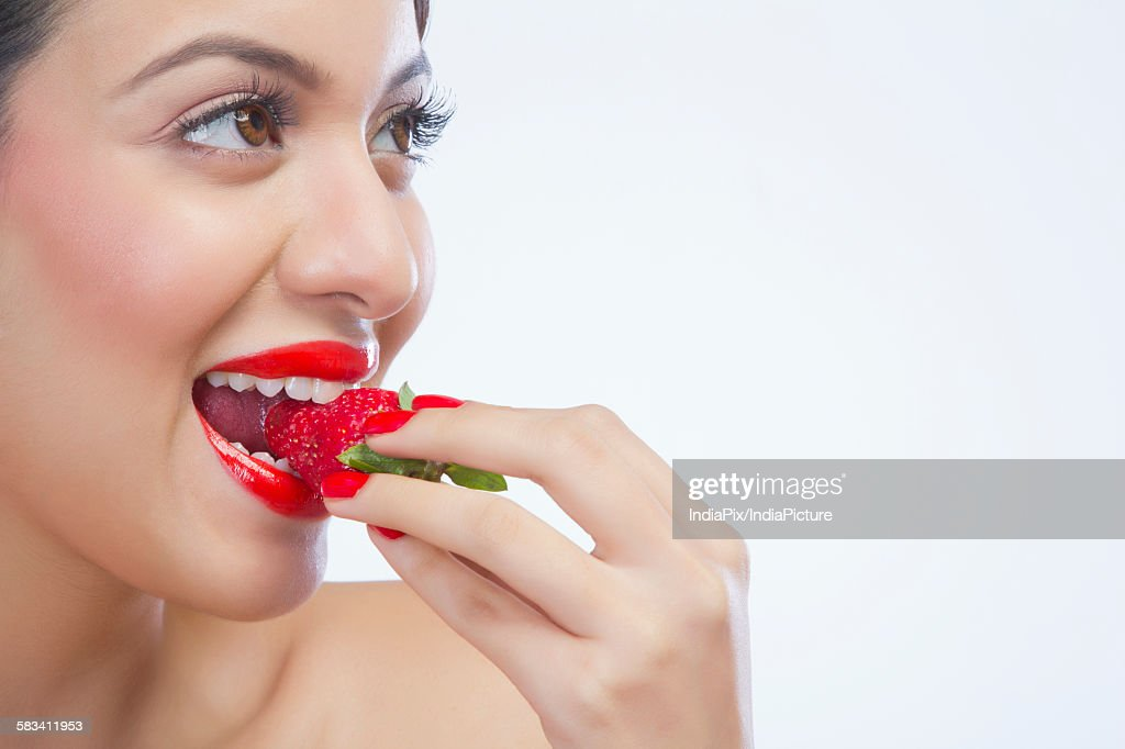 Woman eating a strawberry : Stock Photo