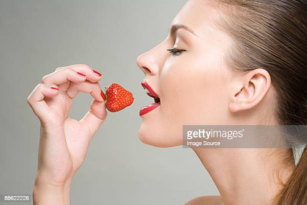 a woman eating a strawberry - essen mund benutzen stock-fotos und bilder