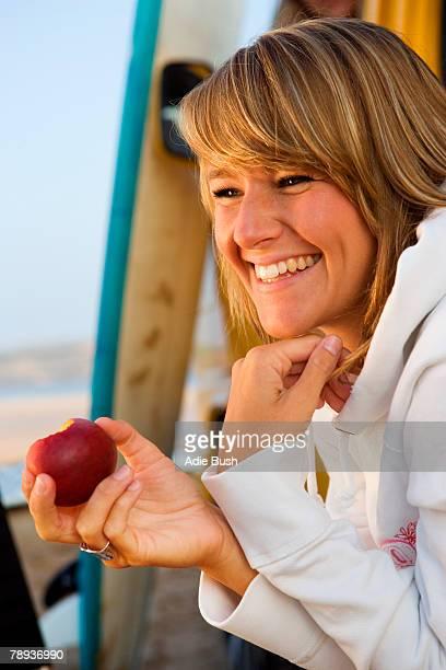 Woman eating an apple near surfboards.