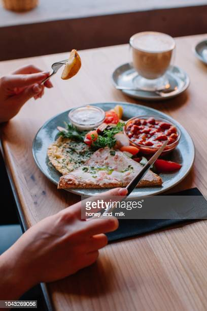 Woman eating an egg and bacon breakfast