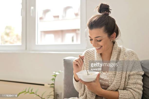 woman eating an oatmeal - oatmeal stock pictures, royalty-free photos & images