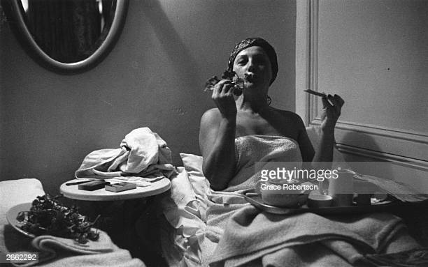 Woman eating, and drinking a cup of tea, in a cubicle at a at the Savoy, a women's turkish bath on Duke of York Street, London, 1951. Original...