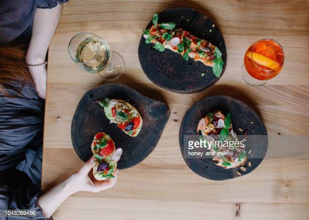 Woman eating appetizers with a glass of white wine and aperol spritz