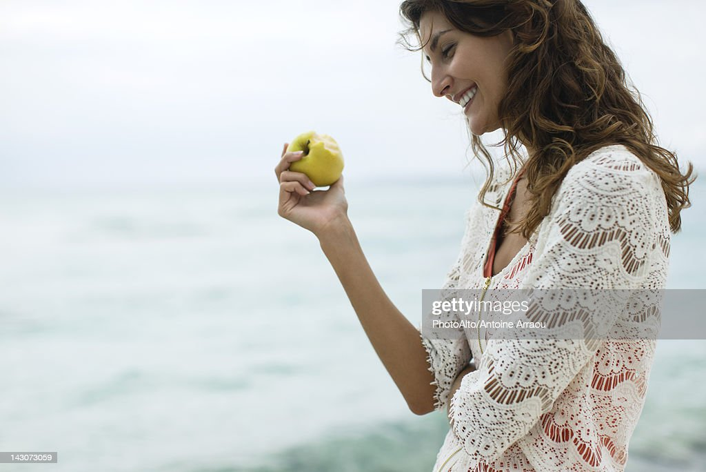 Woman eating apple at the beach : Stock Photo