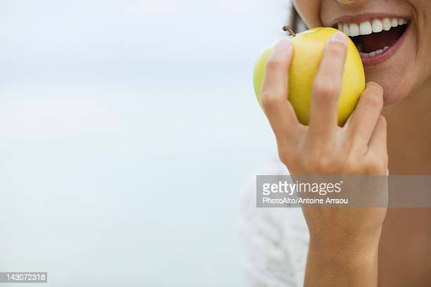 Woman eating apple, cropped
