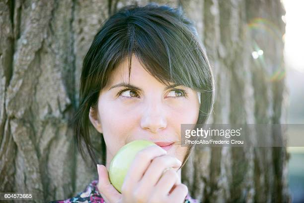 Woman eating apple, looking up thoughtfully