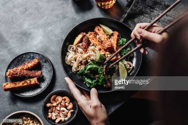 woman eating asian dish with chopsticks - asian food stock pictures, royalty-free photos & images
