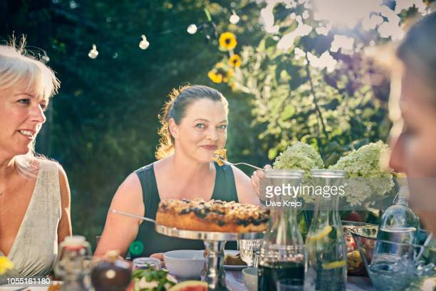 Woman eating at dinner party in garden