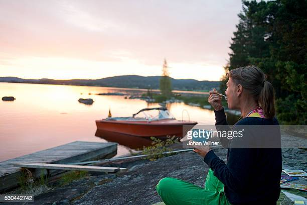 Woman eating at lake, Siljan, Dalarna, Sweden
