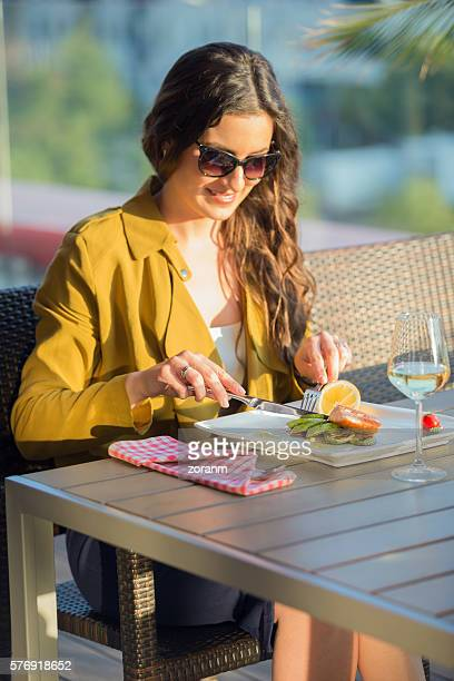 Woman eating at outdoor restaurant