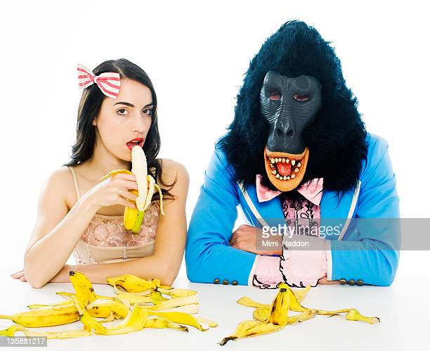 woman eating banana next to sad gorilla man - freaky couples bildbanksfoton och bilder