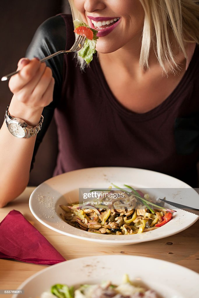 Woman eating bowl of food in cafe : Foto stock